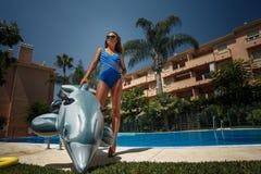 Flicka med den uppblåsbara delfin royaltyfri foto