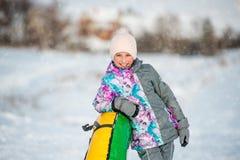 Flicka med den uppblåsbara snösläden på sluttande på vintern Royaltyfria Bilder