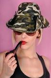 Flicka med det arméhatten och röret Royaltyfri Foto