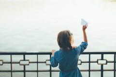 Flicka med det pappers- flygplanet för leksak som ser till sjön Royaltyfri Foto