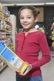 Flicka med det sädes- paketet i supermarket fotografering för bildbyråer