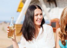 Flicka med drinken och vänner på stranden arkivfoto