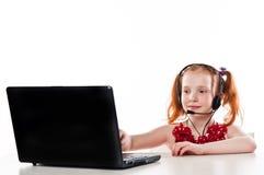 Flicka med en bärbar dator och en hörlurar med mikrofon arkivfoton