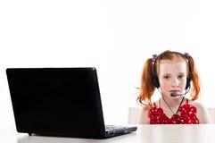 Flicka med en bärbar dator och en hörlurar med mikrofon royaltyfri bild