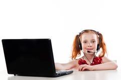 Flicka med en bärbar dator och en hörlurar med mikrofon arkivbild