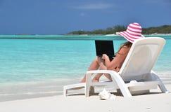 Flicka med en bärbar dator på den tropiska stranden Arkivfoton