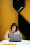 Flicka med en bärbar dator på tabellen Royaltyfri Bild