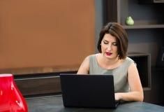 Flicka med en bärbar dator på tabellen Fotografering för Bildbyråer