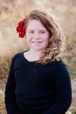 Flicka med en blomma i hennes hår arkivfoton