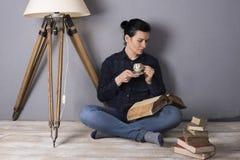 Flicka med en bok och ett kaffe Fotografering för Bildbyråer