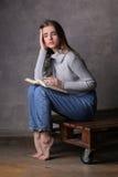 Flicka med en boka Grå färgbakgrund Royaltyfria Bilder