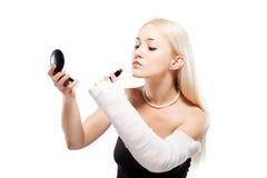 Flicka med en bruten arm som försöker att sätta makeup Arkivbilder