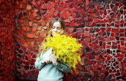 flicka med en bukett av gula blommor av mimosan i hennes händer arkivfoto