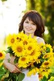 Flicka med en bukett av solrosor Royaltyfri Bild