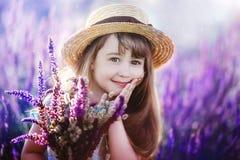 Flicka med en bukett i händer i ett lila fält Arkivfoton