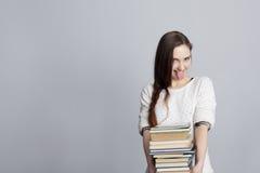 Flicka med en bunt av böcker som visar tungan arkivfoton