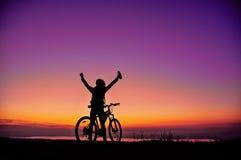Flicka med en cykel som håller ögonen på solnedgången Arkivbilder