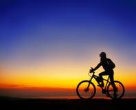 Flicka med en cykel som håller ögonen på solnedgången Royaltyfria Foton