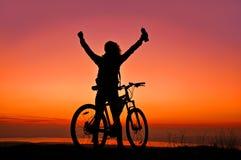 Flicka med en cykel som håller ögonen på solnedgången Fotografering för Bildbyråer