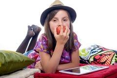 Flicka med en digital minnestavla och ett äpple Royaltyfri Foto