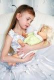 Flicka med en docka Fotografering för Bildbyråer