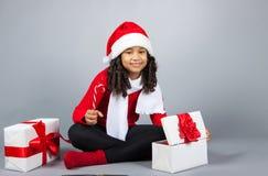 Flicka med en gåva för nytt år Glad flicka i ett lock av Santa Claus Fotografering för Bildbyråer