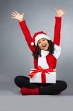 Flicka med en gåva för nytt år Glad flicka i ett lock av Santa Claus Royaltyfri Foto
