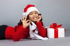 Flicka med en gåva för nytt år Glad flicka i ett lock av Santa Claus Royaltyfri Fotografi