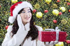 Flicka med en gåva nära julträd Arkivbilder