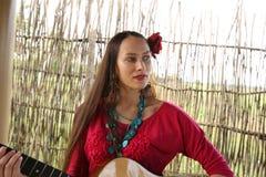 Flicka med en gitarr och en röd ros i hennes hår arkivfoto