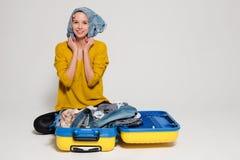 Flicka med en gul resväska Arkivfoton