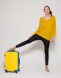 Flicka med en gul resväska Arkivbild