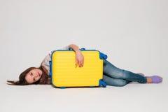 Flicka med en gul resväska Royaltyfri Foto
