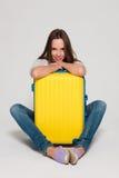 Flicka med en gul resväska Arkivbilder