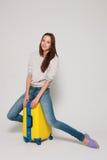 Flicka med en gul resväska Royaltyfri Bild