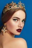 Flicka med en guld- krona och guld- örhängen Arkivfoto