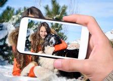 Flicka med en hund i snön Fotografering för Bildbyråer