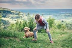 Flicka med en hund på en äng arkivfoton