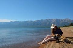Flicka med en hund på kusten av Lake Baikal royaltyfri foto