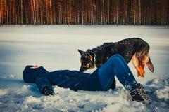 Flicka med en hund på kusten av en vintersjö royaltyfri bild