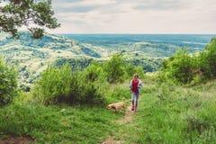 Flicka med en hund som promenerar en fotvandra slinga royaltyfri bild
