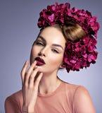 Flicka med en idérik frisyr och blomstrablommor arkivfoto