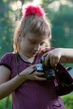 Flicka med en kamera i natur Arkivfoton
