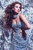 Flicka med en klänning med juvlar Arkivbild