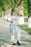 Flicka med en klockaringklocka i henne händer Tid ledning T arkivbild