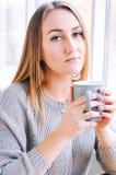 Flicka med en kopp kaffe eller ett te arkivfoto