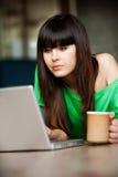 Flicka med en kopp nära datoren Arkivbilder
