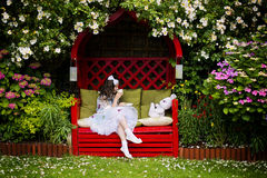 Flicka med en kopp te i trädgård royaltyfria bilder