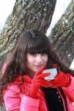 Flicka med en kopp te i vinterskogen Arkivfoto