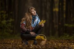 Flicka med en korg och lönnlöv arkivfoton